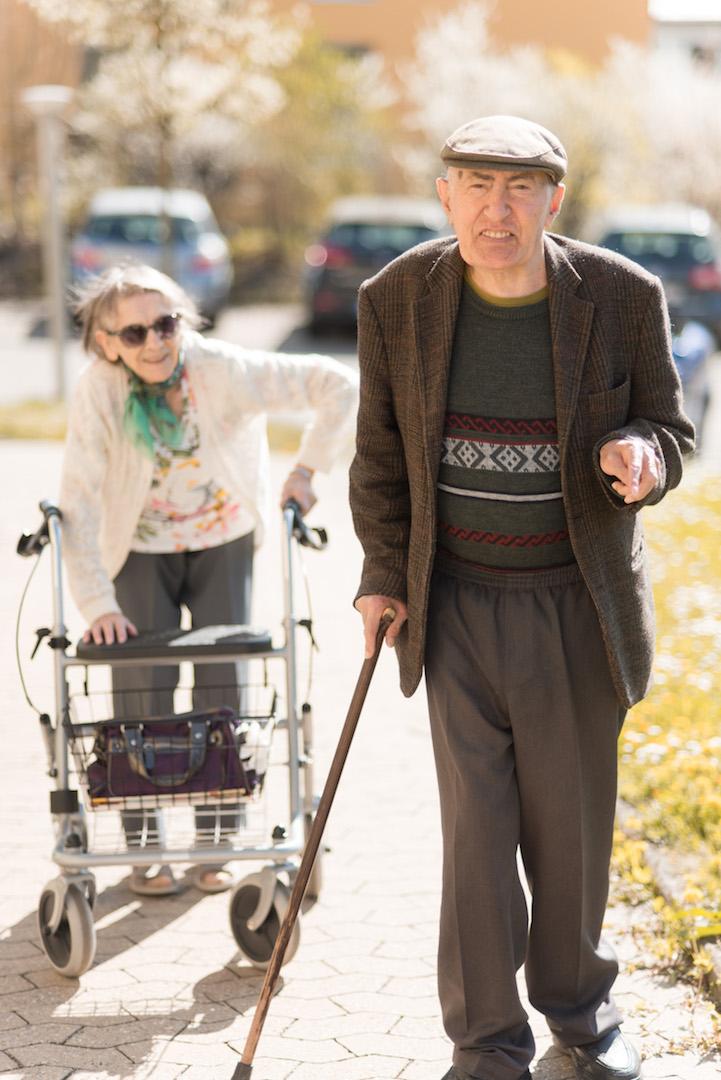 Eine Seniorin und ein Senior von Haus Heimweg gehen im Park spazieren