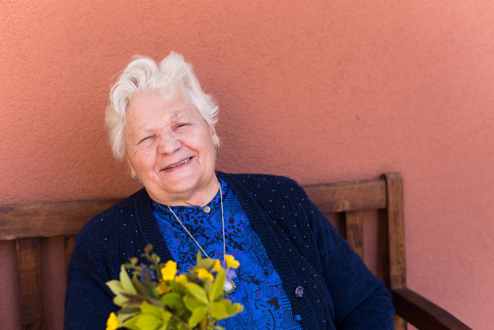 Eine Seniorin sitzt auf der Bank im Hof