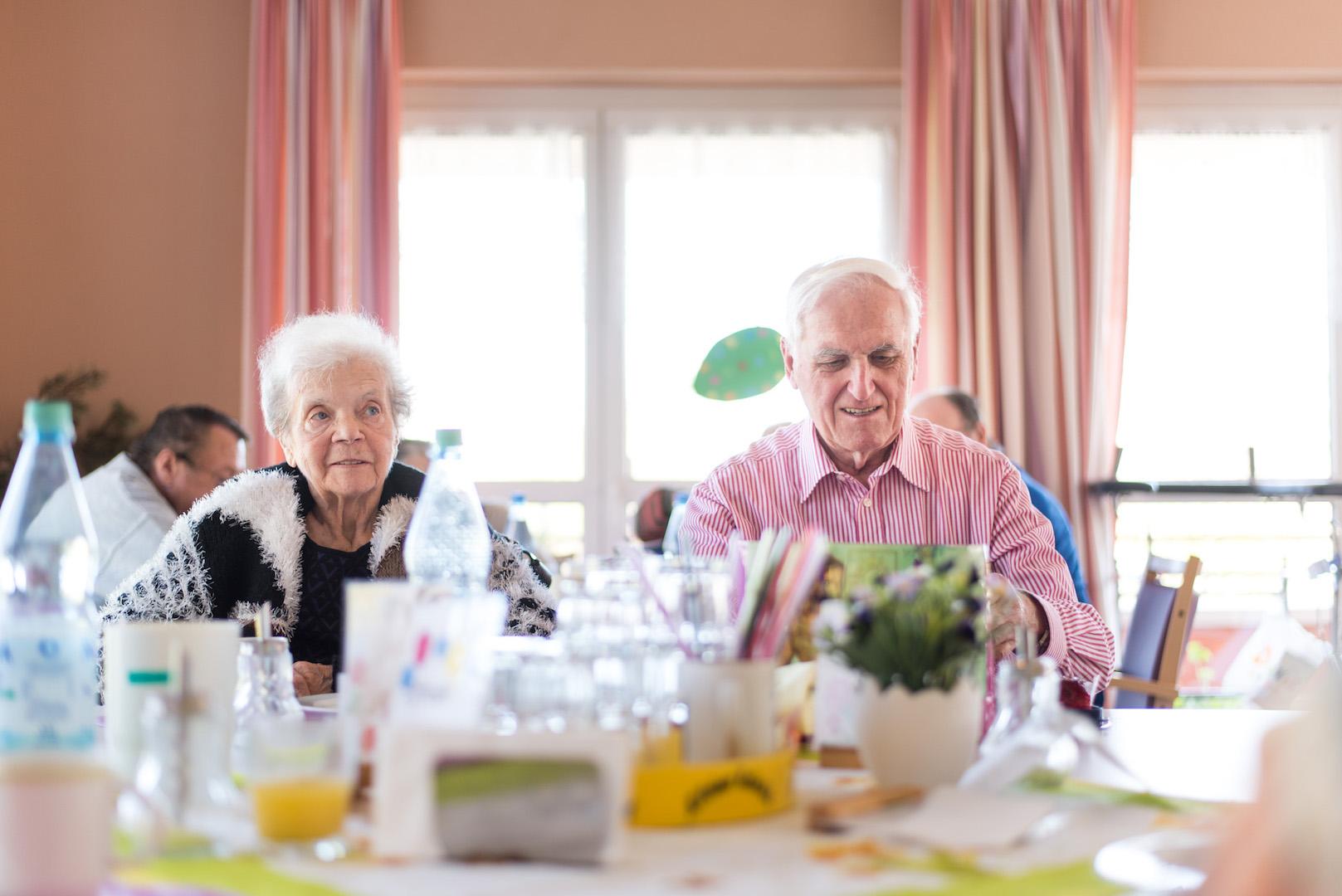 Eine Bewohnerin und Ein Bewohner sitzen am Frühstückstisch.