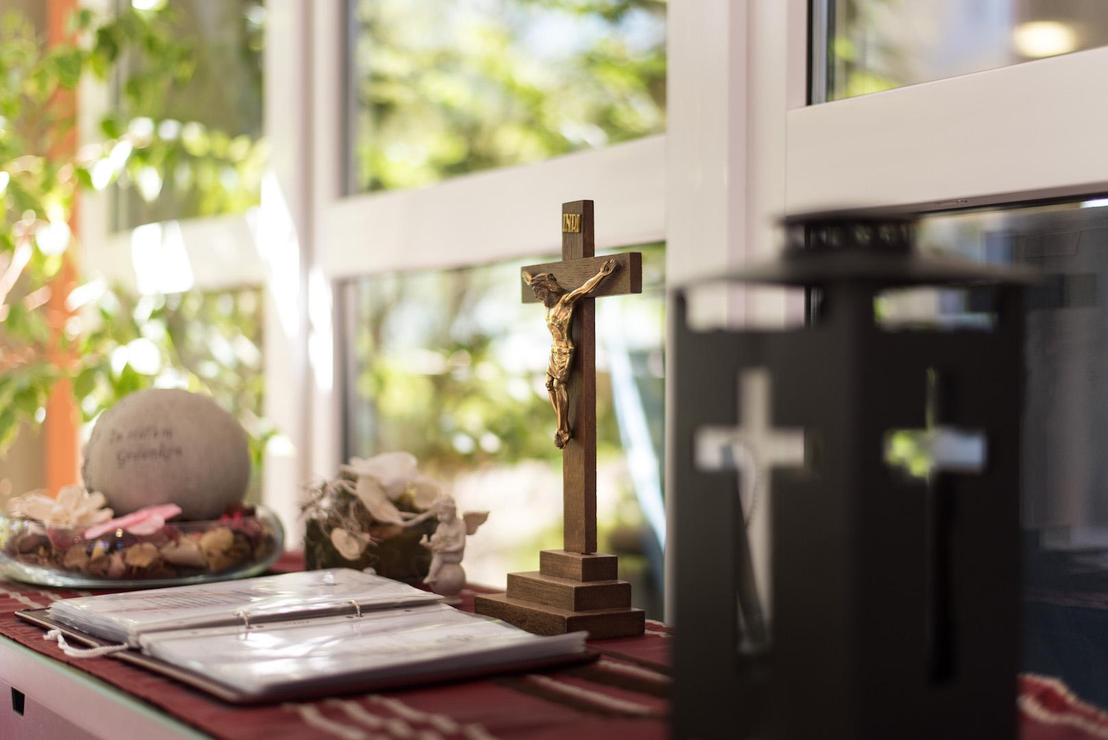 Die Trauerecke mit einem Kreuz, einem Gedenkstein und einem Trauerbuch.